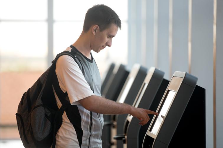 Gutt sjekker inn på flyplass. Foto