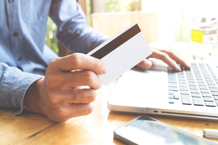 Kredittkort i hånden foran pc. Foto