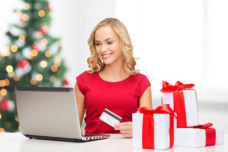 Kvinne foran pc med kredittkort. Foto