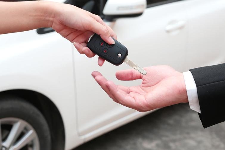 Bil i bakgrunn og bilnøkler i hånden. Foto
