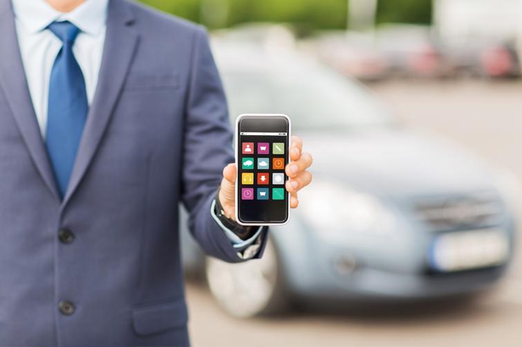 Mann med mobil med bil bak. Foto