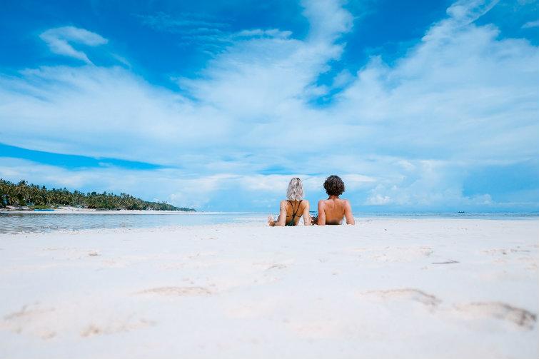 To personer ligger på stranda. foto.